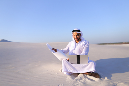 Handsome male Arab businessman and construction worker uses computer for design, busy developing complex schemes and opens drawing for checking and clarifying details sitting on white sand in bottomless wide desert in afternoon against blue sky. Swarthy M Stock Photo