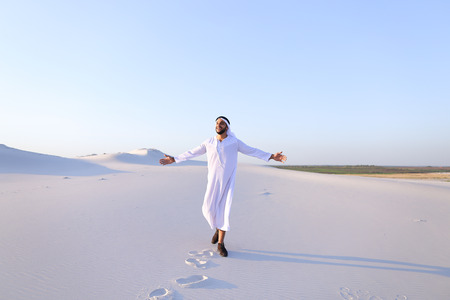 Successful Muslim tourist guy smiles broadly and spreads hands to sides and whirls around, laughs and smiles in desert on clear warm day. Swarthy, handsome Muslim with short dark hair dressed in kandura, long, spacious dress made of white unpainted cotton Stock Photo