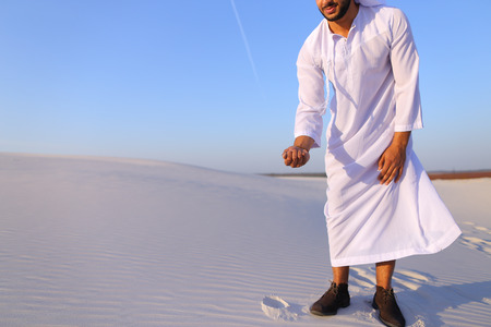 Happy young Emirati Sheikh bends over and takes white sand in hands, rises up and lets sand through fingers of hands, smiling on face, standing in midst of bottomless desert with white sand on hot sunny day. Swarthy handsome Muslim with short dark hair is Stock Photo