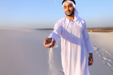 Close-up of face and hands of young Muslim man who takes sand into hand and blows small white grains of sand through fingers, guy smiles and looks out into distance of bottomless desert on hot summer day. Swarthy, handsome Muslim with short dark hair dres Stock Photo