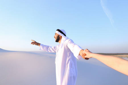 Cheerful Arab male with kindly smile on face leads womans arm from camera and shows desert landscapes, conducts outing in middle of bottomless sandy desert with white clean sand against blue sky in open air. Swarthy, handsome Muslim with short dark hair d