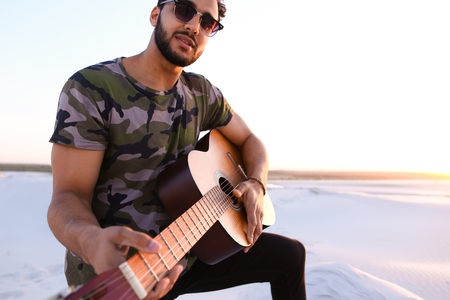 Romantic bearded young Arab man exercises musical instrument with strings, smiles and becomes comfortable in position to start playing guitar, standing in middle of wide sandy desert on warm summer evening at sunset. Swarthy man with dark hair and short h