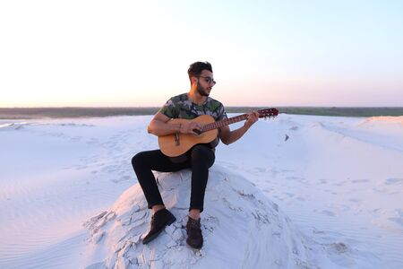 Handsome guy, Arab playing with pleasure on musical stringed instrument and with beautiful smile on face. Man sings and drives guitar strings, sitting on hill in middle of wide sandy desert on warm summer evening at sunset. Swarthy man with dark hair and