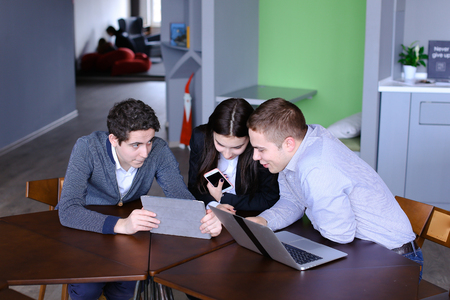 immersed: Managers of firm are concentrated and immersed in device and sit at table in their spare time at companys office. guys are using laptop and tablet, girl holding in hands and reading news with help of mobile. European-looking guy with fair hair and short h