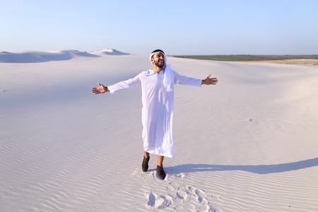 potěšen: Úžasný mladý šék chodí pěšky po bezedné poušti, takže zanechá stopy na písku a těší se teplo dne. Atraktivní muslim se široce usmívá a rozšiřuje se rukama po stranách, narovnává oblečení ve větru a otáčí kolem sebe, potěšen širokostí pouště. Snědý,