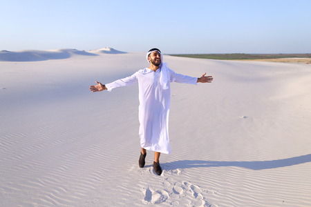 breadth: Stately young sheikh walks on foot along bottomless desert leaving traces on sand, enjoying warmth of day. Attractive Muslim smiles widely and spreads hands to sides, straightens clothes in wind and whirls around, delighted by breadth of desert. Swarthy,  Stock Photo