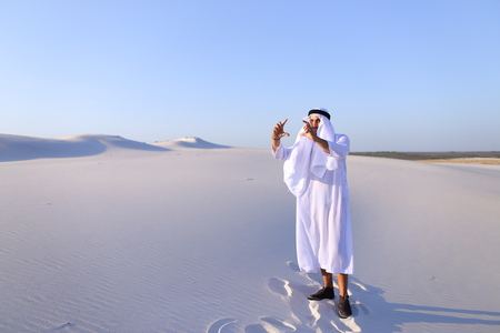Confident Muslim guy stands full-length in middle of bottomless desert with white sand and thinks how to make beautiful photo of landscape better, looking for successful frame with hands, smiling with beautiful smile. Swarthy Muslim with short dark hair d