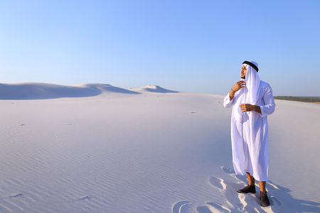 Serious young Arab man peers into distance and tries to see caravan of camels walking, puts hand to forehead defensively against bright sun in hot wide desert with white sand on clear summer day. Swarthy Muslim with short dark hair dressed in kandura, lon Stock Photo