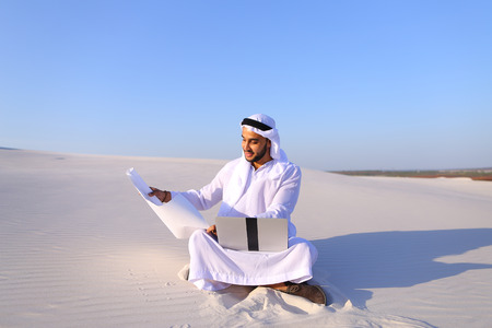 clarifying: Handsome male Arab businessman and construction worker uses computer for design, busy developing complex schemes and opens drawing for checking and clarifying details sitting on white sand in bottomless wide desert in afternoon against blue sky. Swarthy M Stock Photo