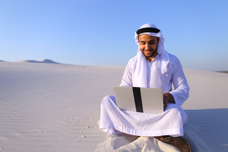 Successful young businessman male Muslim uses laptop to build drawing in Photoshop and prints fingers on laptop sitting on white sand in bottomless wide desert in afternoon against blue sky. Swarthy Muslim with short dark hair dressed in kandura, long, sp Stock Photo