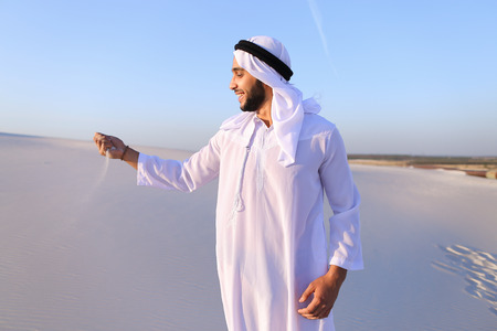 Young Arab guy who takes sand in hand and lifts it to smiling face and blows through fingers fine white grains of sand in bottomless desert on hot summer day. Swarthy, handsome Muslim with short dark hair dressed in kandura, long, spacious dress made of w