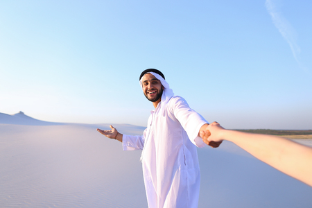 Cute Muslim young man and tourist guide with smile on face leads girl by hand from camera and tells interesting information about travel and shows desert neighborhood, in middle of bottomless sandy desert with white clean sand against blue sky in evening