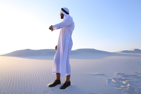Attractive guy, emirate businessman uses for business and for work iWatch, who are put on hand, smiling and examining landscapes of large sandy desert against blue sky on hot summer morning. Swarthy Muslim with short dark hair dressed in kandura, long, sp