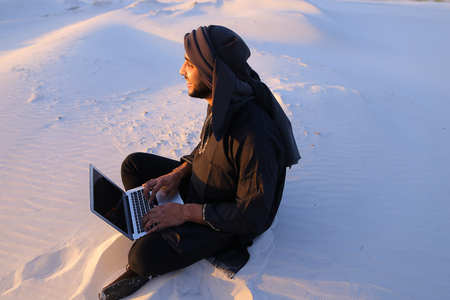 Joyous male Arab sits on sand at computer. young man engaged in scientific work or writes article typing on keyboard of gadget, relaxes sitting in silence of bottomless desert against blue sky on summer evening. Swarthy Muslim with short dark hair and bea
