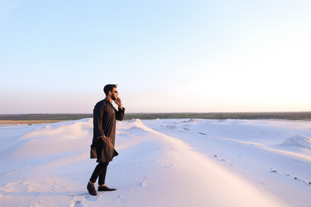 Young fellow Arabian traveler calls on mobile friend and with smile on face tells about seen beautiful landscapes and impressions, standing in middle of bottomless desert with white sand on warm summer evening. Swarthy Muslim with short dark hair and wear Stock Photo