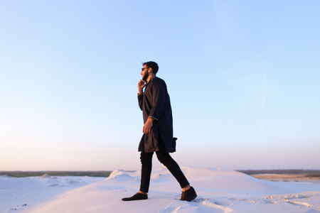 Handsome Muslim businessman conducts dialogue on smartphone with business partner and tells ideas for progressing matters or solves important work issues while standing in middle of bottomless desert with white sand on warm summer evening. Swarthy Muslim  Stock Photo