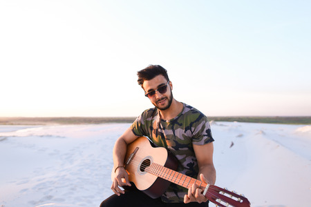 Handsome Arabian guy plays tune on guitar, drives strings and sings song, sitting on hill in middle of wide sandy desert on warm summer evening at sunset. Swarthy man with dark hair and short haircut in sunglasses dressed in camouflage t-shirt, black pant Stock Photo
