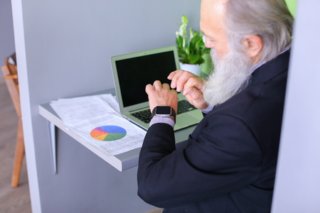 Senior publishes latest phrases on computer and introduces amendments to business plan and completes workflow, checks notifications of calls on iWatch watches sitting at table in modern office. Elderly man with long gray beard of European appearance dress Stock Photo