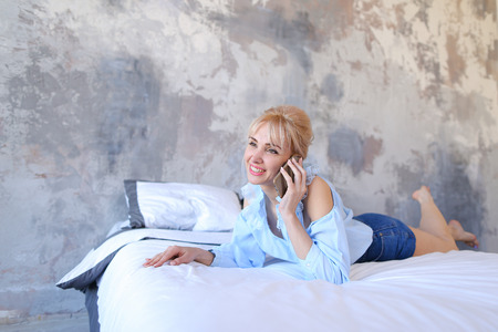 Nice woman holding smartphone in hands and conducting dialogue on phone with girlfriend or guy