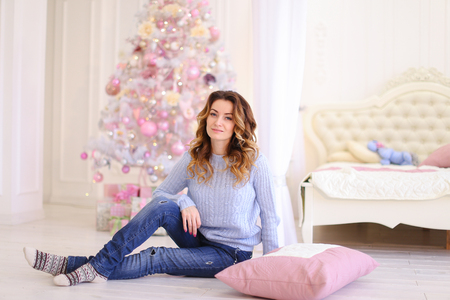 Elegant female smiling and posing near  pillow for photo in memory in festive bright bedroom