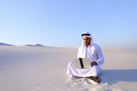 build in: Successful young businessman male Muslim uses laptop to build drawing in Photoshop and prints fingers