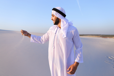 Young Arab guy who takes sand in hand and lifts it to smiling face Stock Photo