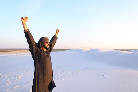 Handsome Emirate man walks white sand of desert, smiles broad smile and looks around neighborhood.
