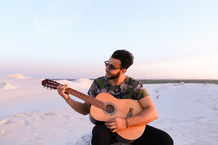 Bearded Muslim young man enthusiastically plays guitar Stock Photo