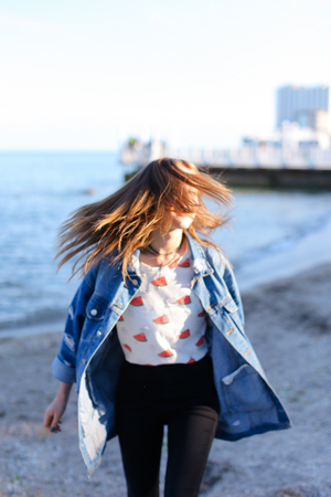 Charming girl resting and with beautiful smile on face posing in camera, laughing and enjoying beautiful day on shore of blue sea. Woman of European appearance with blond mid-length hair dressed in blue denim jacket and stands with back to camera lens aga