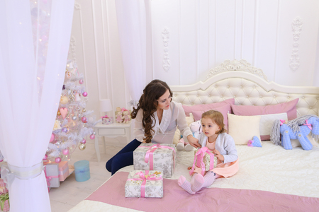 Lovely woman, caring mother showing little girl how to pack presents and tying ribbons. Family on threshold of New Year holidays, and women laugh gently kissing and hugging baby daughter. Cute female with long dark wavy hair dressed in dark jeans and tran