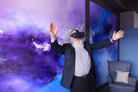 bl: Man in old age sweeps at high speed along trajectory and virtually rolls on roller coaster, feels ecstatic and happy with use of modern VR glasses, talks and smiles with hands spread apart. Old man with long gray beard of European appearance dressed in bl Stock Photo