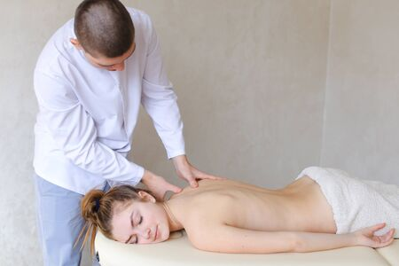 back ache: Stately guy therapist and masseur drives hands on girls back and relieves tension in spine.