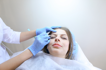 Microblading specialist, beautiful girl, makes imitation of eyebrows with sharp special needle on face of female client with light brown hair in blue cap that rests on white couch in modern day salon. Stock Photo