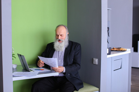 interbank: Senior citizen analyzes financial situation of company and conducts operations on interbank loans market using computer and negotiating bluetooth headset while sitting in stylish office cafe on sunny day. Elderly man with long gray beard of European appea