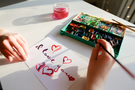 The woman writes letter I love you in creative calligraphic font and creates romantic card with brush and watercolor paint, sitting at white table on which there paints and glass jar for water in studio. European-looking girl dressed in brown sweater with Reklamní fotografie