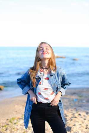 sweetly: Lovely girl poses positively on camera in perfect mood, smiles and laughs sweetly, slowly approaches very shore of water
