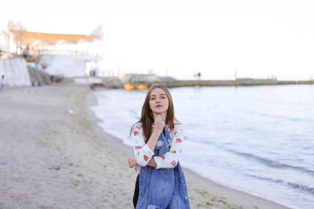approaches: Lovely girl poses positively on camera in perfect mood, smiles and laughs sweetly, slowly approaches very shore of water, squints from sun and admires incredible scenery around, standing on beach of sandy beach on warm summer evening at sunset. Stock Photo