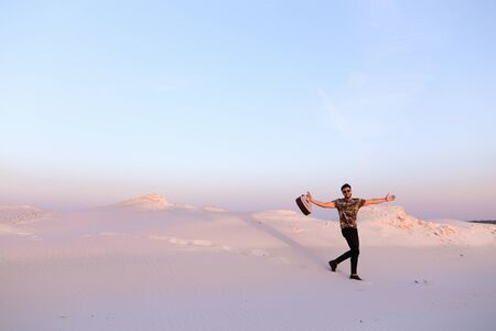 Young Muslim male performer and singer walks through sandy desert with guitar in hands.