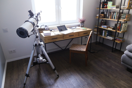 Internal conditions and arrangement of working area and office in bright and spacious room. In room there wooden simple table with metal black supports on which there laptop and notebooks and diaries, wooden chair with soft upholstery, large minimalist bo