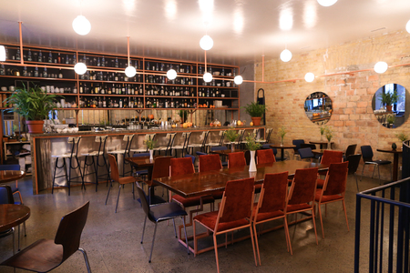 Cozy quiet and warm lighting restaurant with brick walls, white ceiling and big and tall rectangular windows. In hall of cafe or restaurant located usually simple wooden tables and chairs covered with varnish. Concept of modern and trendy restaurants and