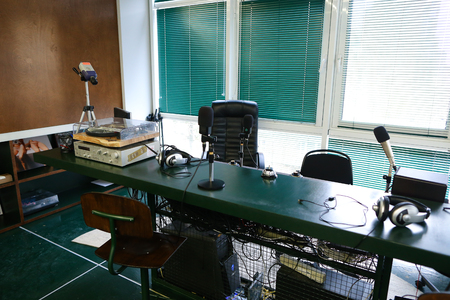 Taking Close-up in studio. Devices for recording of radio microphones and mixing consoles, broadcast processor and special devices on wooden table in radio studio with big windows ponoramic. Concept of radio studio and online broadcast, equipment device r