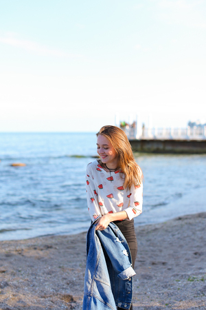 Smiling female walks along beach and enjoys nature, with broad smile on face jumping in place and raising hands upwards, squinting against bright sunlight, shielding eyes with hands. Stock Photo