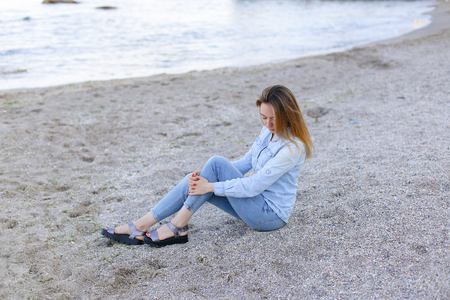 Happy girl looks at camera with beautiful and sweet smile, enjoying pleasant pastime, sitting on beach and looking toward endless blue sea on pleasant evening.