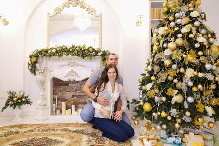 tenderly: Lovers man and woman, young family tenderly embrace each other and kiss, pose for photograph sitting on carpet near beautiful decorated Christmas tree and fireplace with candles in bright and comfortable room. Stock Photo