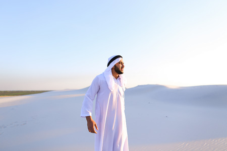 Frustrated fellow emirate suffers from back pain and holds on to waist, feels heaviness and tries to stretch back to improve condition, standing in middle of bottomless desert with white sand on sunny summer day.