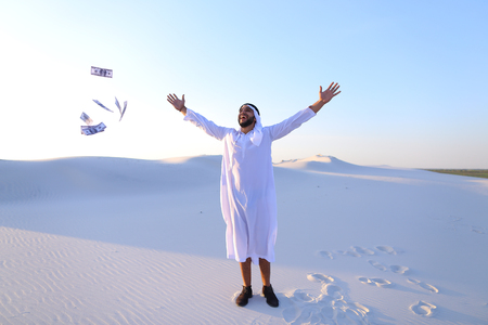 Stately young male Arab man in good mood conducts financial training of money, smiles and laughs joyfully launches money to wind, standing in middle of bottomless desert with white sand on sunny summer day.