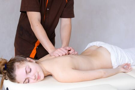 back ache: Stately male therapist and practicing masseur make compressing movements backbone massage, relieves fatigue and tension with help of medical procedure