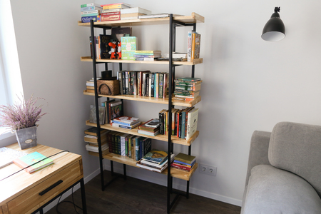 Details of interior of office in bright and spacious room. In room minimalist bookcase with wooden shelves and black metal opals on which there large number of scientific and general educational books with magazines. Cabinet with large white window and wh Editorial