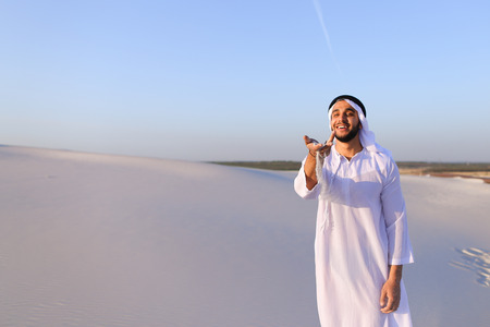 Young Arab guy who takes sand in hand and lifts it to smiling face and blows through fingers fine white grains of sand in bottomless desert on hot summer day. Stock Photo
