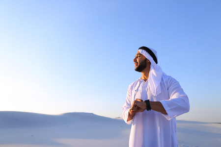 Attractive guy, emirate businessman uses for business and for work watch, who are put on hand, smiling and examining landscapes of large sandy desert against blue sky on hot summer morning. Stock Photo